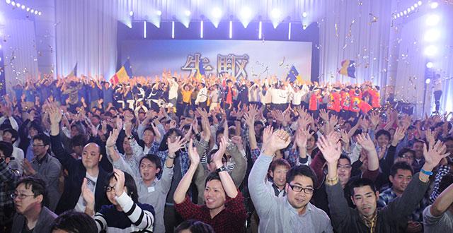 九州池田講堂に集う九州男子部のメンバー。階段に設営された「先駆」の文字が迎える