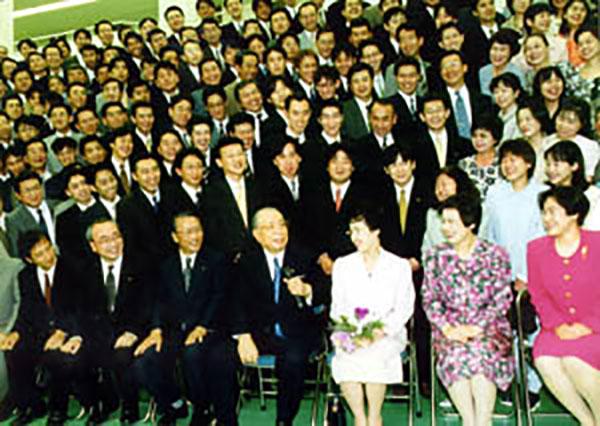 九州の「創価教育同窓の友」との記念撮影で、メンバーを励ます創立者・池田大作名誉会長(1999年5月、九州池田講堂)