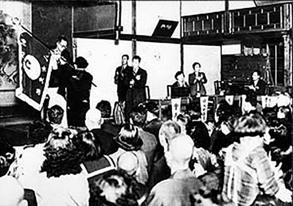 九州初の支部旗が、戸田第2代会長から手渡された(写真左)(1953年3月、八女公会堂)